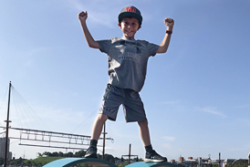 Jadon posing in a champion stance atop a large metal heart sculpture at Baltimore's Inner Harbor