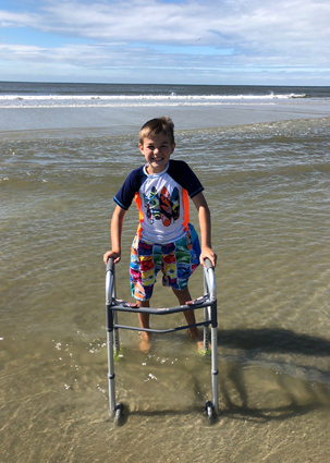 Preston in shallow water at the beach while using his walker
