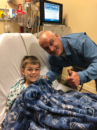 Preston smiling in a hospital bed being visited by Dr. Standard who is making a thumbs up sign