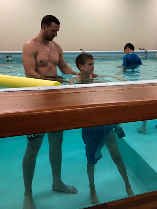 Preston wearing an external fixator while doing hydrotherapy with a physical therapist at the Rubin Institute's Rehabilitation Department