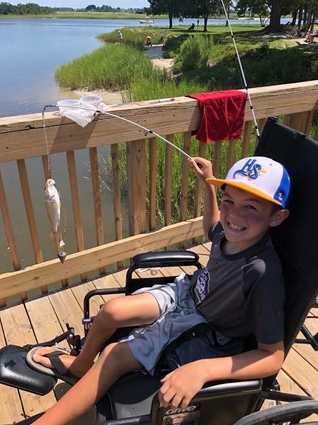 Preston with a fish he caught from his wheelchair by a lake
