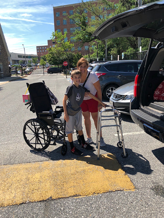 Preston and his mom with his wheelchair and walker in the parking lot at the Hackerman-Patz House