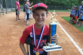 Preston on crutches on a baseball field with a medal and trophy