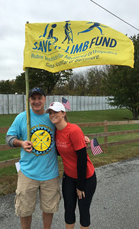 Rachael and Dr. Standard with Save-A-Limb flag at walk event