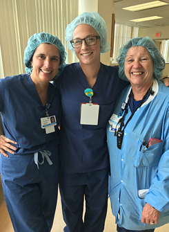 Rachael in scrubs with RIAO nurses during a shadowing visit
