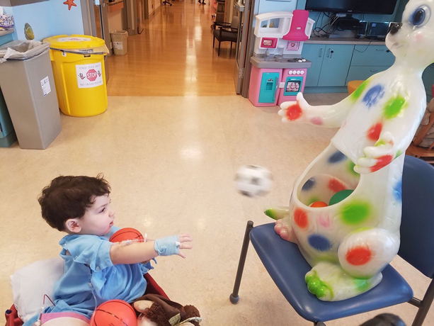 Ross playing a ball toss game while sitting in a wagon at the Herman & Walter Samuelson Children's Hospital