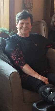 Sharon smiling while seated in a chair with an ankle boot on