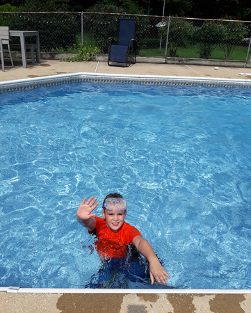 Wyatt waving while in a swimming pool waving