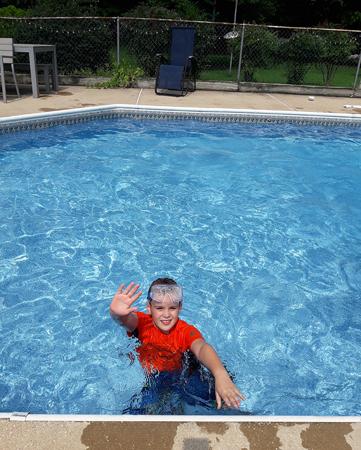 Wyatt waving while in a swimming pool waving