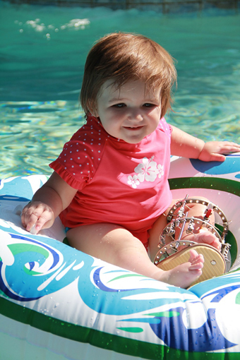 Emma as a toddler wearing an external fixator on one leg in a float in a pool