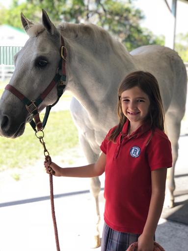 Emma leading a white horse