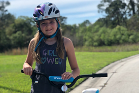 Emma in a Girl Power t-shirt and helmet with a bicycle