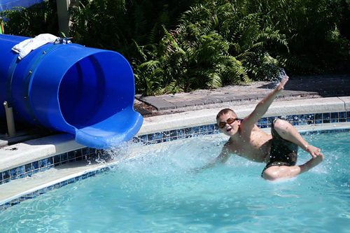 Matt in midair shooting out of a swimming pool tube slide before his second surgery