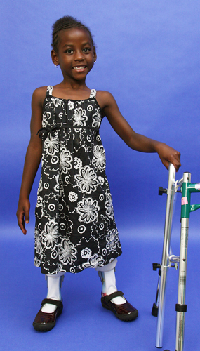 Melissa standing with leg braces and walker