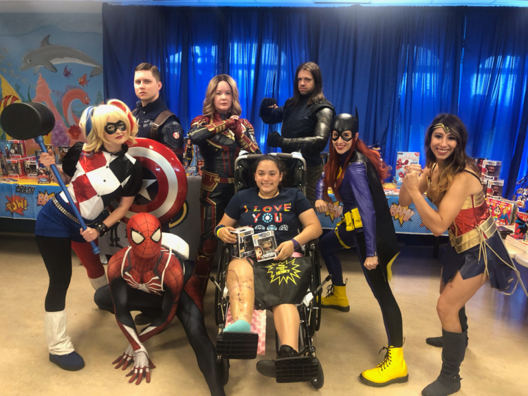 Girl patient in Wheelchair holding superhero bobbleheads posing with superheroes Wonder Woman, Bat Girl, Iron Man, Captain Marvel, Captain America and Spiderman and villain Harley Quinn