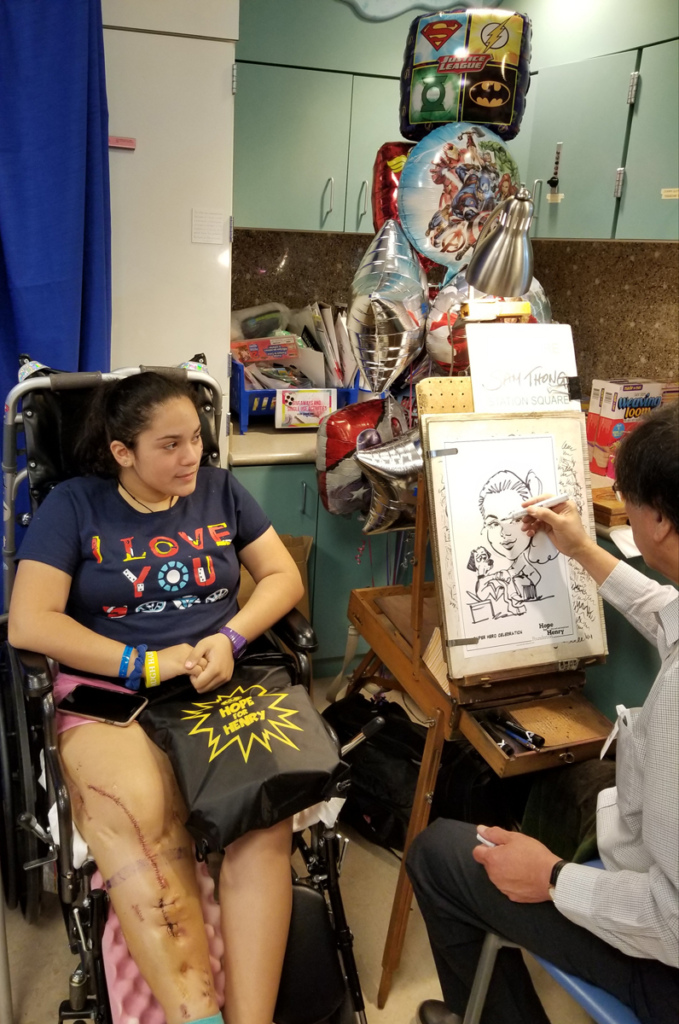 Girl patient in wheelchair sitting by superhero balloons while a caricature artist draws her with a dog