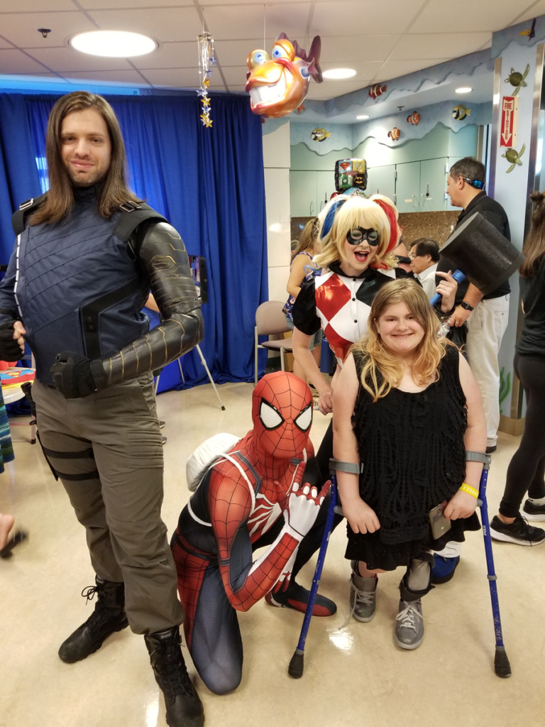 Girl patient with forearm crutches posing with Harley Quinn, Iron Man, and Spiderman