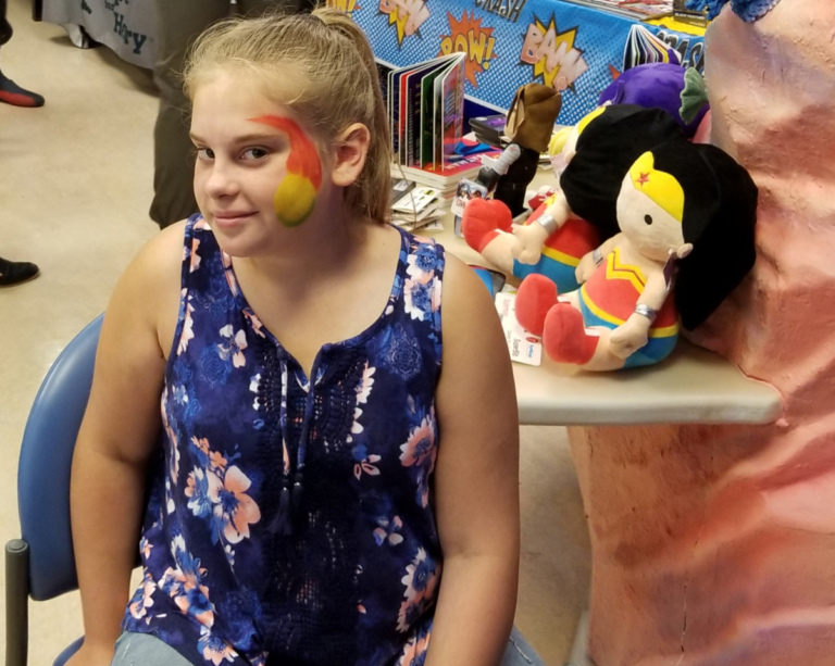 Girl Patient getting her face painted by a table of stuffed plush Wonder Woman toys
