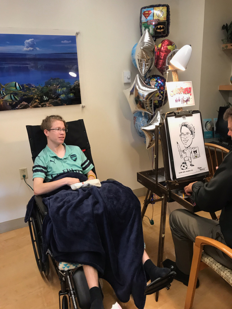 Boy patient in wheelchair sitting while a caricature artist draws him