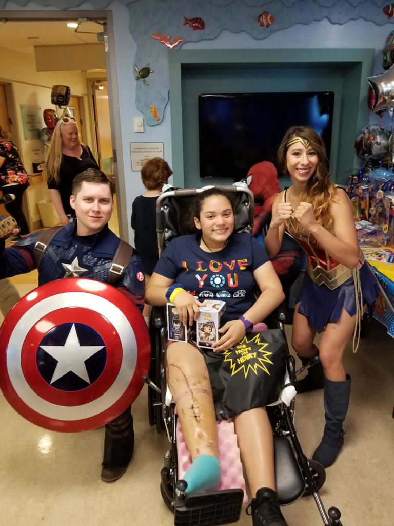 Girl patient in wheelchair with Captain America and Wonder Woman