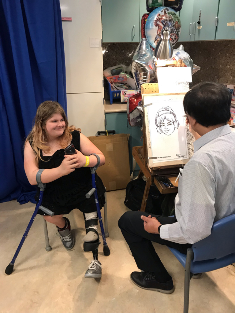 Girl patient with forearm crutches sitting while a caricature artist draws her