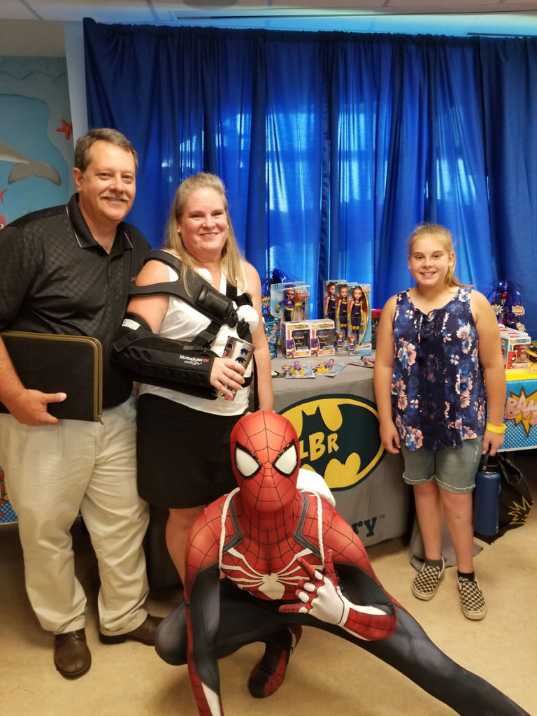 Girl patient and parents posing with Spiderman in front of table of Superhero toys for patients