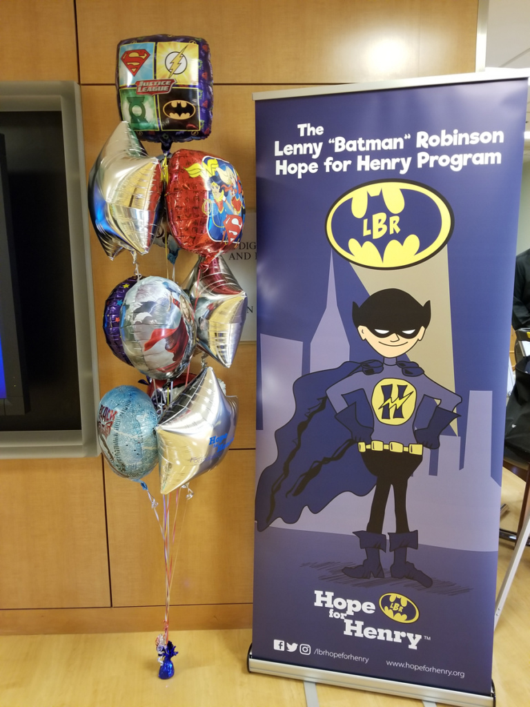 "Sign with cartoon Batman and LBR Batman light signal that says ""The Lenny 'Batman' Robinson Hope for Henry Program"" by mylar helium superhero balloons"