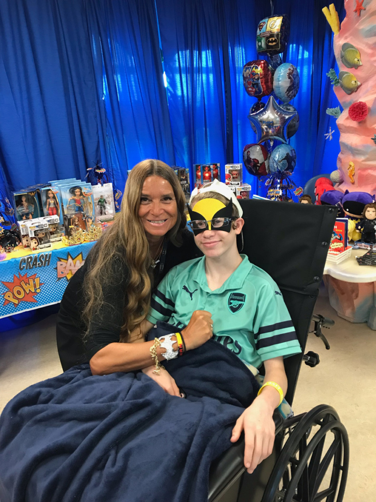 Boy patient in wheelchair wearing superhero mask with Marilyn Richardson, Pediatric Liaison in front of table of superhero toys for patients