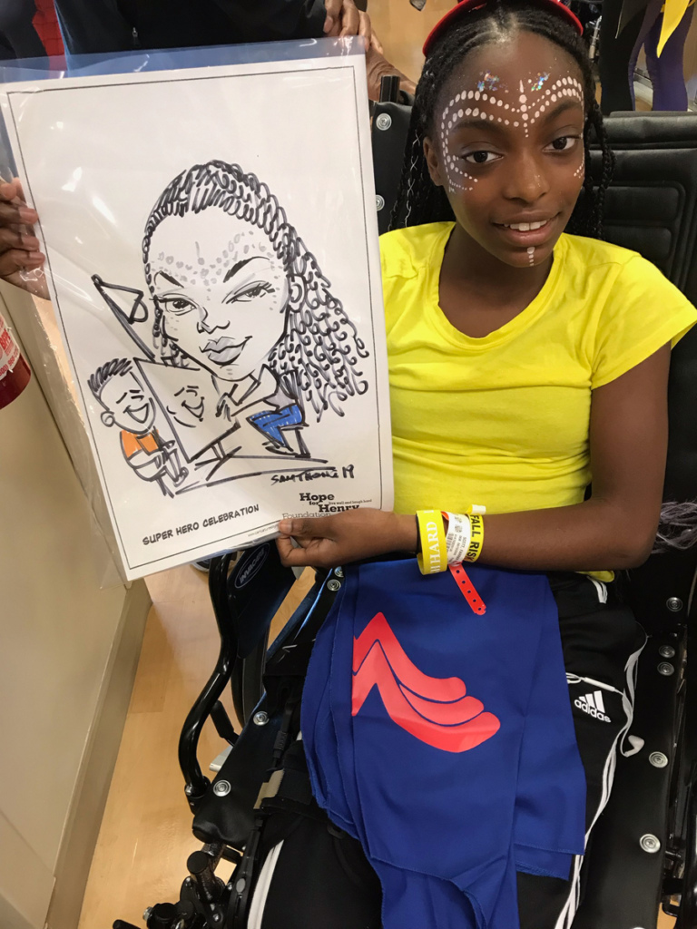 Girl patient in wheelchair wearing face paint and holding up a caricature of herself drawing