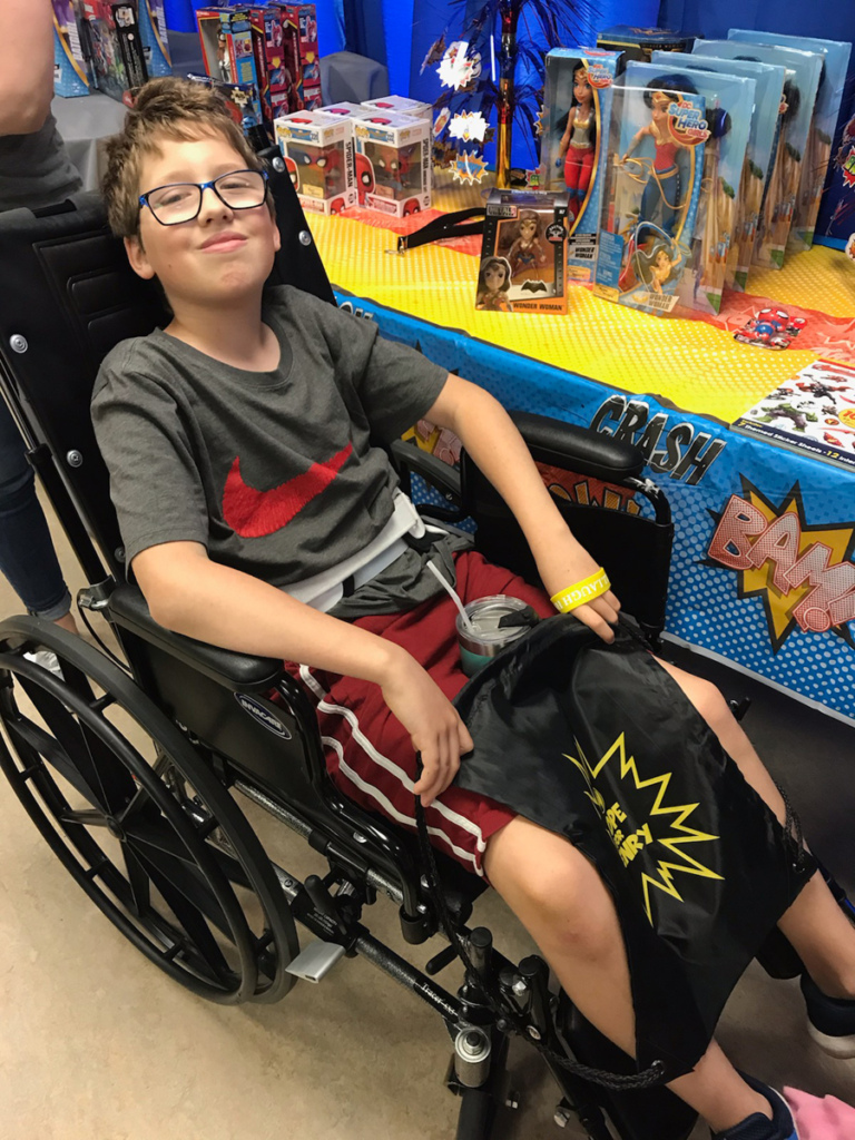 Boy patient in wheelchair with LBR Hope for Henry bag to fill with 3 superhero toys of his choice by a table of superhero toys