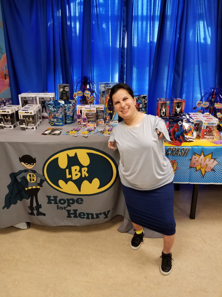 Female patient by LBR Hope for Henry Batman logo on a table full of superhero toys