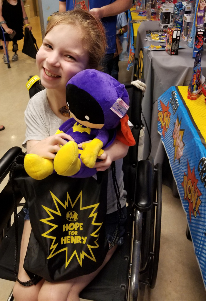 Girl patient in wheelchair smiling while holding up a stuffed plush Batgirl toy