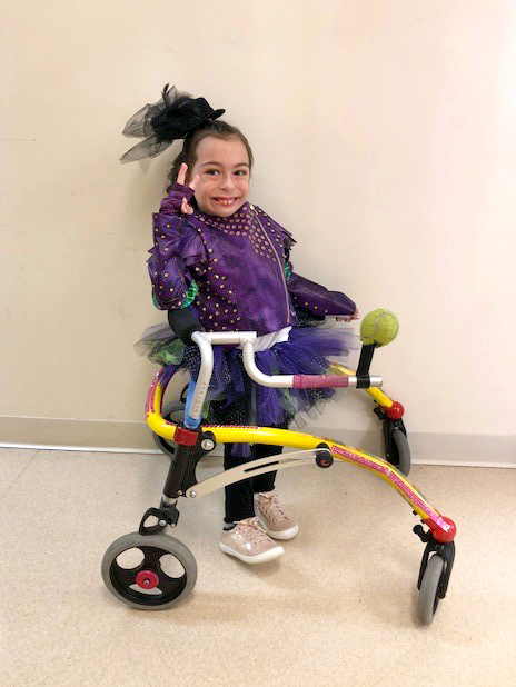 Alena in a purple and black tulle costume making a peace sign and using a wheeled-gait trainer walking aid
