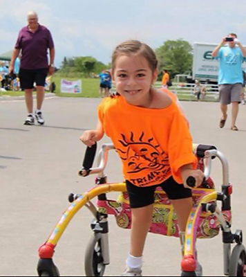 Alena participating in a triathalon with her wheeled-gait trainer walking aid