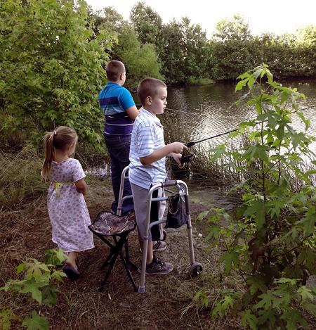 Wyatt fishing at a lake while using a walker
