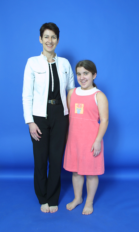 Hannah in her early teens standing next to her mother before her lengthening surgery; she is shorter than her mother's shoulders.