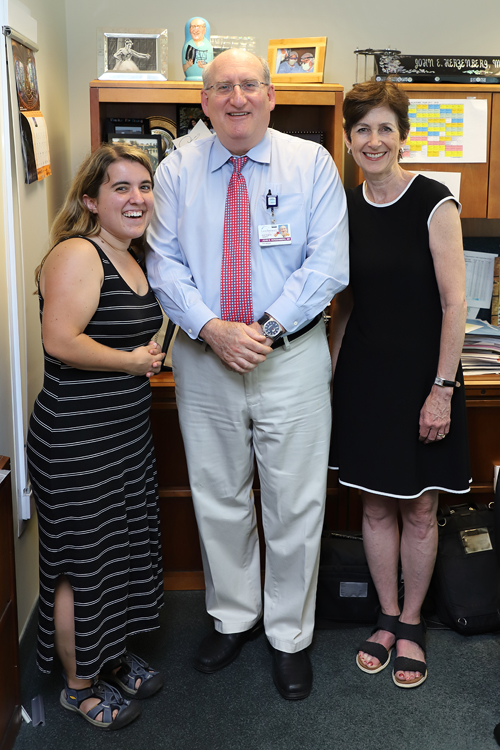 Hannah and her mother standing with Dr. Herzenberg in 2018; Hannah now reaches much higher than her mother's shoulders--closer to the height of her mother's nose.