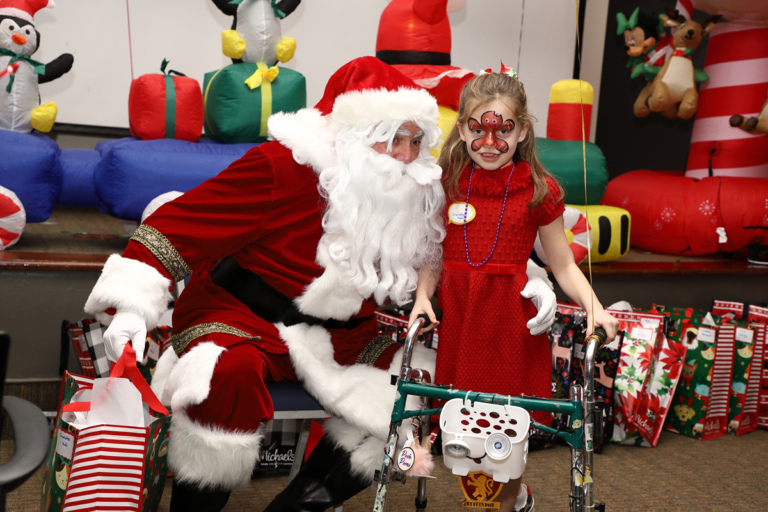 Young girl with gingerbread man face paint using a walker next to Santa Claus