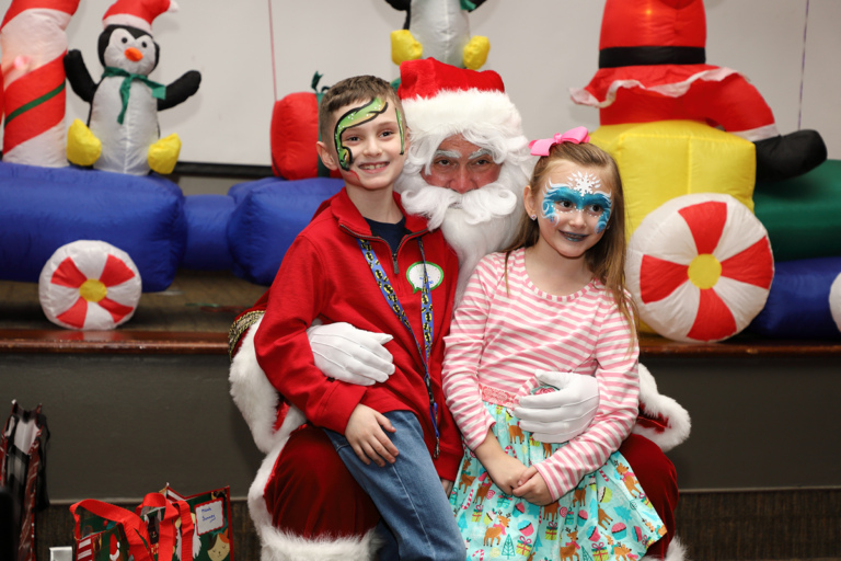 Girl and boy with face paint smiling on Santa's lap