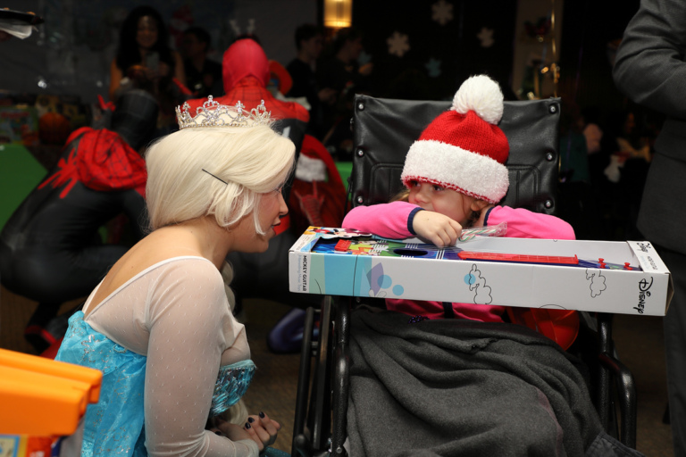 Young girl in wheelchair with a toy talking with a Disney Princess