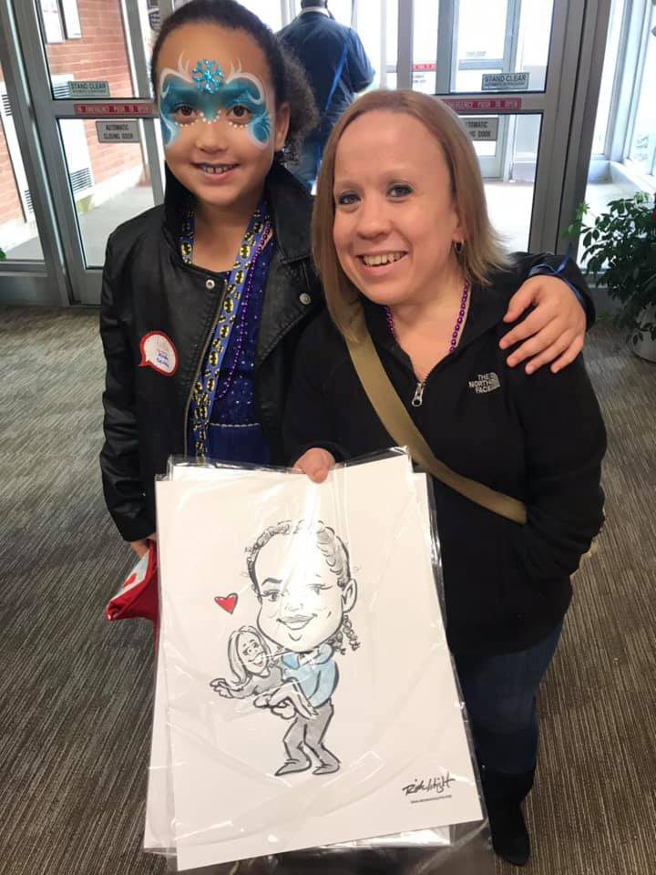 Mother and daughter smiling and showing off a caricature