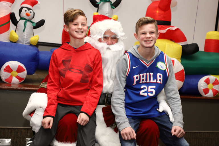 2 boys smiling on Santa's lap