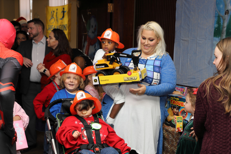 Mother holding little boy wearing orange firefighter hat and Deere Big Scoop truck with four other children wearing firefighter hats