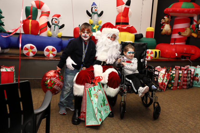 Face-painted boy and girl in a wheelchair smiling with Santa Claus
