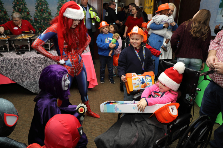 Girl in wheelchair with toy talking with comic book superheroes and villains with children with toys and firefighter hats in the background