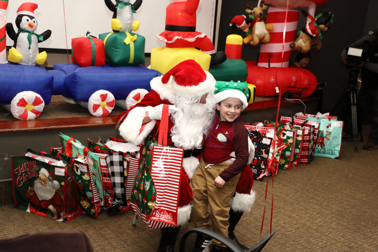 Boy in Christmas tree hat smiling on Santa's lap getting a gift bag