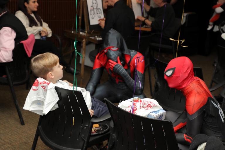 Boy sitting being visited by Spidermen