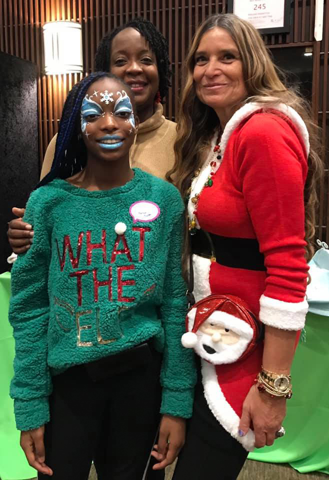 Mother and daughter with face painted with Marilyn Richardson, Pediatric Liaison, all smiling