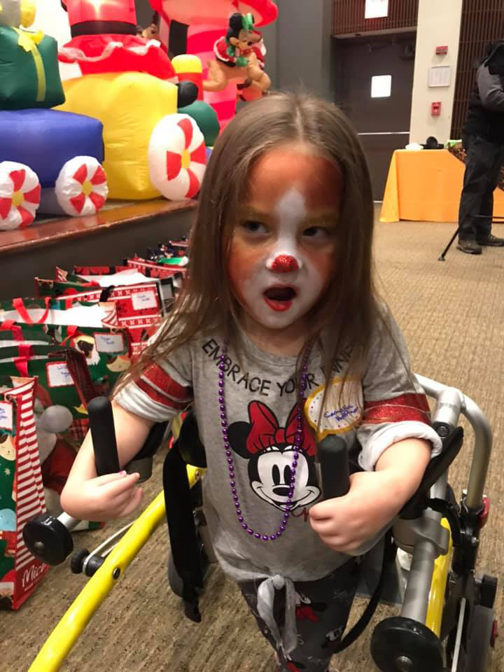 Young girl with Rudolph face paint standing with the support of an assisted device