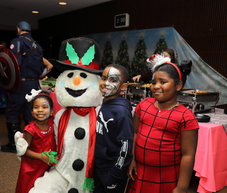 2 young girls and a boy smiling with Frosty the Snowman